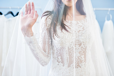 Buy stock photo Cropped shot of an unrecognizable bride fitting her wedding gown in a bridal shop