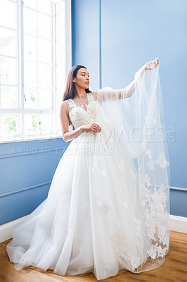 Buy stock photo Full length shot of a beautiful young bride looking at her veil while wearing her wedding gown in her dressing room