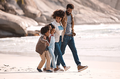Buy stock photo Shot of an adorable little boy and girl going for a walk along the beach with their parents