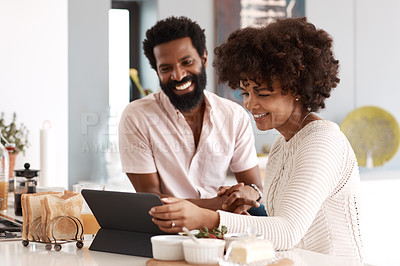 Buy stock photo Shot of a couple looking at something on a digital tablet while having breakfast at home