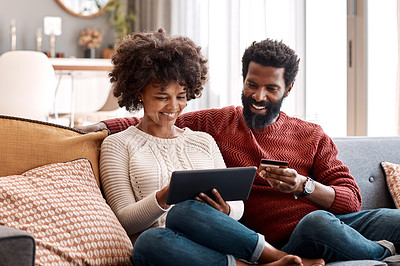 Buy stock photo Shot of a man holding a credit card while browsing on a digital tablet with his wife