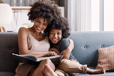 Buy stock photo Shot of an adorable little boy reading a book and spending time with his mother at home