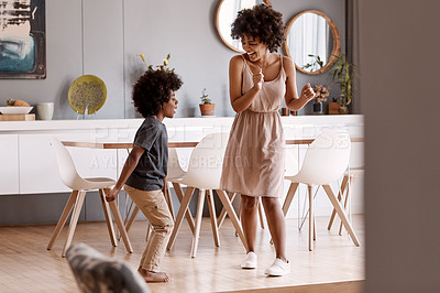 Buy stock photo Full length shot of a happy young mother and son dancing together at home