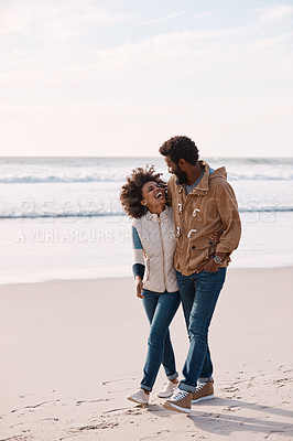 Buy stock photo Shot of a happy young couple going for a romantic walk along the beach