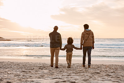 Buy stock photo Rearview shot of an adorable little boy watching the sunset at the beach with his grandfather and father