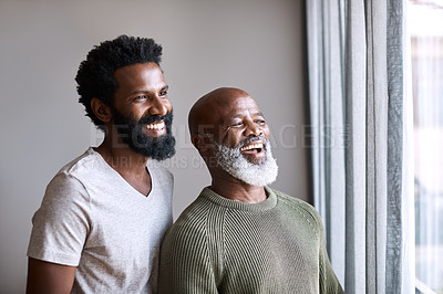 Buy stock photo Shot of a happy young man and his father looking out the window together at home