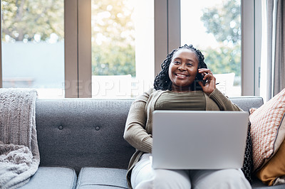 Buy stock photo Shot of a mature woman talking on a cellphone while using a laptop at home