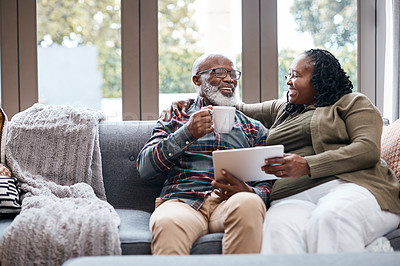 Buy stock photo Shot of a mature couple using a digital tablet while relaxing together on a sofa at home