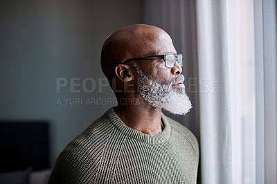 Buy stock photo Shot of a mature man looking thoughtfully through a window at home