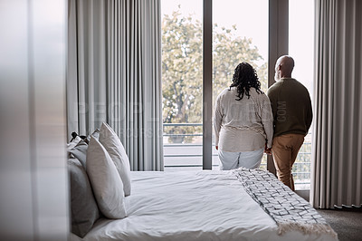 Buy stock photo Rearview shot of a mature couple looking through a window in a bedroom at home