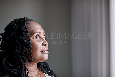 Buy stock photo Shot of a mature woman looking thoughtfully through a window at home
