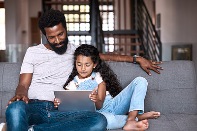 Buy stock photo Shot of an adorable little girl using a digital tablet while bonding and spending time with her father at home