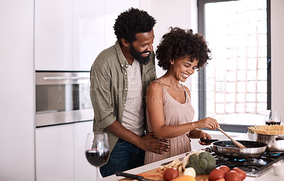 Buy stock photo Shot of a man embracing his wife while she cooks