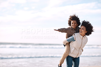 Buy stock photo Shot of an adorable little boy having a fun day at the beach with his mother