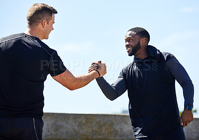 Buy stock photo Cropped shot of two sporty young men shaking hands while out for a run