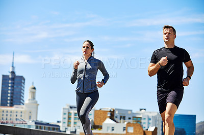 Buy stock photo Shot of two sporty young people out for a run in the city