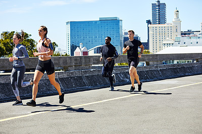 Buy stock photo Shot of a group of sporty young people out for a run in the city