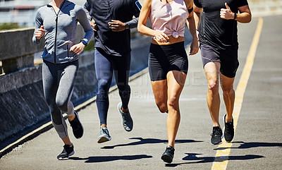 Buy stock photo Cropped shot of a group of sporty young people out for a run in the city