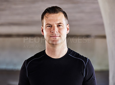 Buy stock photo Cropped portrait of a handsome young male athlete working out in the city