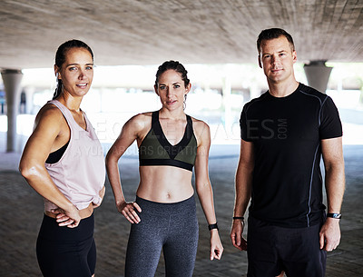 Buy stock photo Cropped portrait of three young athletes standing side by side while working out in the city