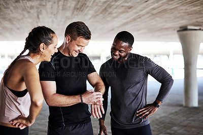 Buy stock photo Cropped shot of three young athletes talking and checking their times while working out in the city