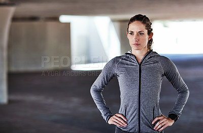 Buy stock photo Cropped shot of an attractive young female athlete standing with her hands on her hips while working out in the city