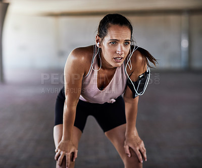 Buy stock photo Cropped shot of an attractive young female athlete resting during her workout in the city