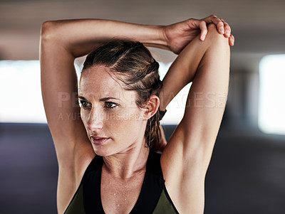 Buy stock photo Cropped shot of an attractive young female athlete stretching during her workout in the city