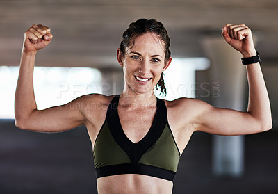 Buy stock photo Cropped portrait of an attractive young female athlete flexing while working out in the city
