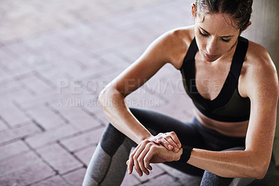Buy stock photo Cropped shot of an attractive young female athlete checking her watch while working out in the city