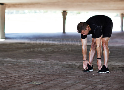 Buy stock photo Full length shot of a handsome young male athlete stretching during his workout in the city