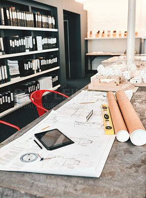 Buy stock photo Still life shot of an architect's blueprints placed on a desk in a modern office
