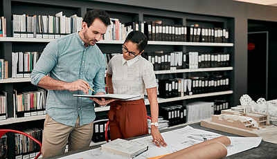Buy stock photo Cropped shot of two aspiring young architects looking at a notebook working together in a modern office