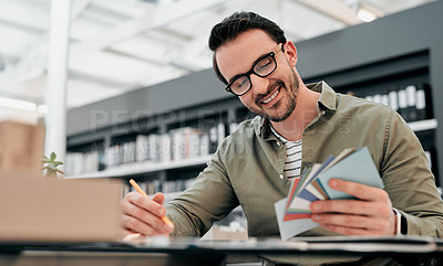 Buy stock photo Cropped shot of a handsome young male architect smiling while looking at a bunch of cards in a modern office