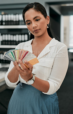 Buy stock photo Cropped shot of a young architect looking at a color swatch while standing in her office