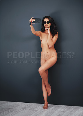 Buy stock photo Studio shot of a gorgeous young woman taking a selfie while posing nude against a grey background