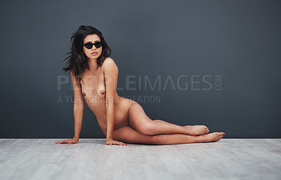 Buy stock photo Studio portrait of a gorgeous young woman posing nude while wearing sunglasses against a grey background