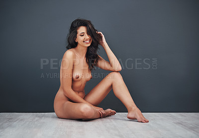 Buy stock photo Studio shot of a gorgeous young woman smiling while posing nude against a grey background