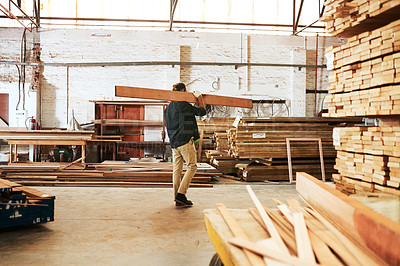 Buy stock photo Full length shot of a young carpenter carrying a wooden plank over his shoulder while working inside a workshop