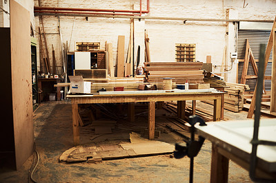 Buy stock photo Still life shot of work tables and piles of wood inside a carpentry workshop