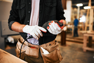 Buy stock photo Cropped shot of an unrecognizable carpenter holding an electric drill inside a workshop