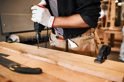 Buy stock photo Cropped shot of an unrecognizable carpenter using an electric drill inside a workshop