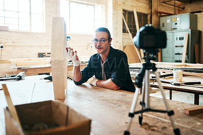 Buy stock photo Shot of young carpenter recording a tutorial of him making a wooden masterpiece on a video camera inside his workshop