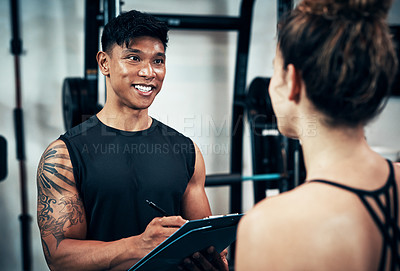 Buy stock photo Shot of a sporty young woman talking to a fitness trainer at the gym