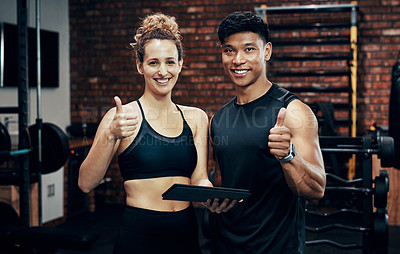 Buy stock photo Cropped shot of two sporty young people holding a digital tablet in the gym