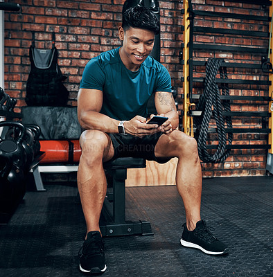 Buy stock photo Cropped shot of a sporty young man using his cellphone at the gym