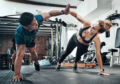 Buy stock photo Shot of two sporty young people working out together at the gym