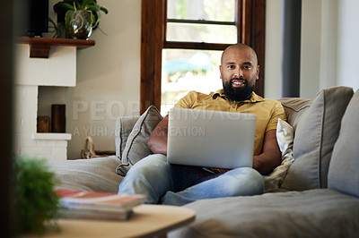 Buy stock photo Cropped portrait of a handsome young man smiling while using a laptop in his living room at home