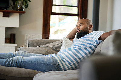 Buy stock photo Cropped shot of a handsome young man relaxing on a couch in his living room at home