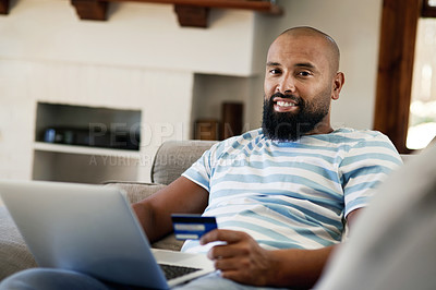 Buy stock photo Cropped portrait of a handsome young man smiling while shopping online in his living room at home